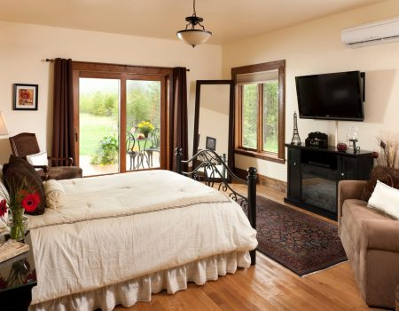 Elegant master bedroom in the Chocolate Suite with Electrical fireplace and view of sliding glass door